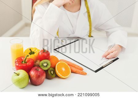 Nutritionist desk with healthy fruits, juice and measuring tape. Dietitian working on diet plan. Weight loss and right nutrition concept, copy space for text