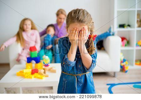 A portrait of a sad little girl in kindergarten