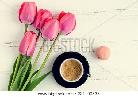 A cup of coffee, almond cookie macaroon and pink tulips on white rustic wooden table. Breakfast on Mothers day, Valentines Day or Womens day. Spring morning concept. Top view.
