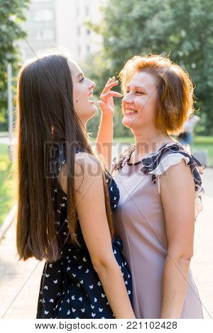 Closeup Portrait of Adult Daughter and Mother Outdoors. Pretty Brunette and Her Mom are Looking at the Camera in the Park in Summer