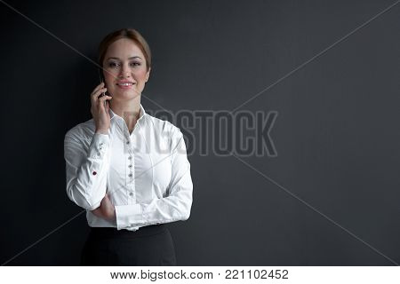 Portrait of beaming lady speaking by mobile while leaning against wall. Communication and business concept. Copy space