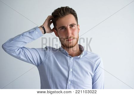 Portrait of confused or pensive young Caucasian businessman or student wearing shirt standing and scratching head. Do not know concept