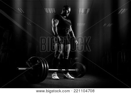 The weightlifter is preparing to perform an exercise called deadlift. He stands directly above the barbell and looks at it.