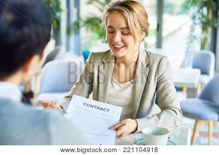 Beautiful young entrepreneur in formalwear discussing contract details with business partner while having productive negotiations at cozy small restaurant