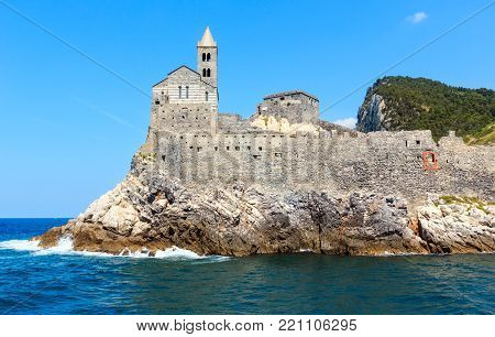 Beautiful medieval fisherman town of Portovenere (UNESCO Heritage Site) view from sea (near Cinque Terre, Liguria, Italy). Church Chiesa di San Pietro.