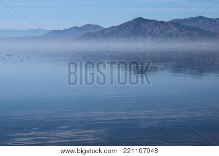 Low lying layer of mist above a lake surrounded by a rural desolate landscape including barren mountains taken in the Salton Sea, CA