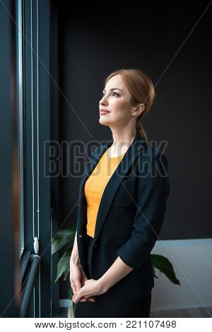 Side view thoughtful lady expressing thoughtfulness while situating in apartment. Break concept