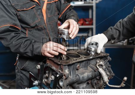 the mechanic installs a new piston. Disassemble engine block vehicle. Motor capital repair. Sixteen valves and four cylinder. Car service concept