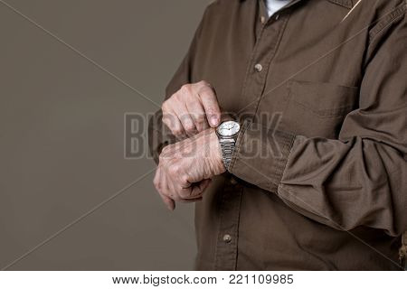 Time is fleeting. close up of wrinkled hand wearing wristwatch. Copy space in left side. Isolated on grey background