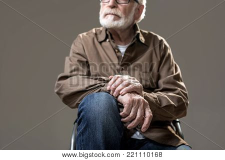 Severe elderly man relaxing on pew. Focus on hands lying on knees. Isolated on grey background