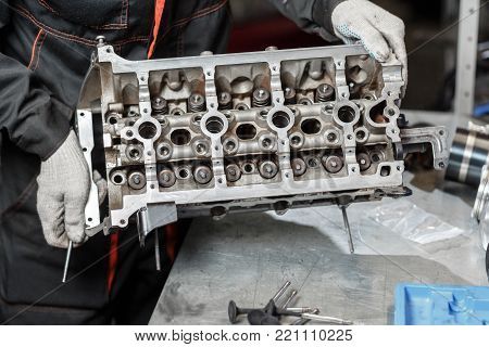 The job of a mechanic. Disassemble engine block vehicle. Motor capital repair. Sixteen valve and four cylinder. Car service concept