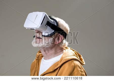 Enchanted male pensioner having fun while using virtual googles. Isolated on grey background