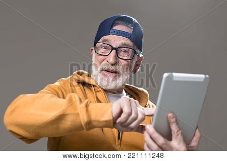 Portrait of happy male pensioner spending free time with advanced technologies. Isolated on grey background