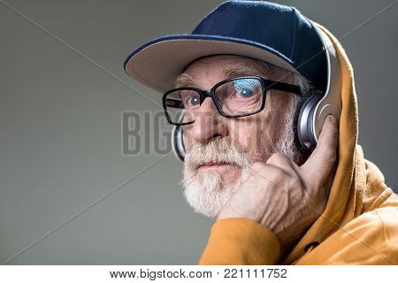 Serious bearded pensioner hearing calm melody in his headphones. Copy space in left side. Isolated on grey background