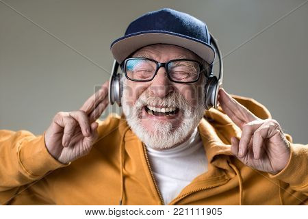 Its brain explosion. Portrait of cheerful elderly man listen to music on headphones. His eyes are closed with pleasure. Isolated on grey background