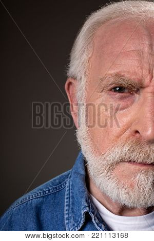 Half face of aging male looking at camera with suspicion. Isolated on grey background. Close up