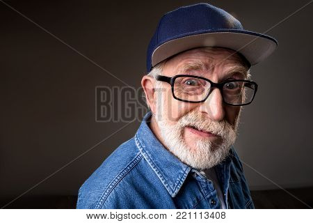 Portrait of humorous senior man gazing at camera and cringing. Standing near wall