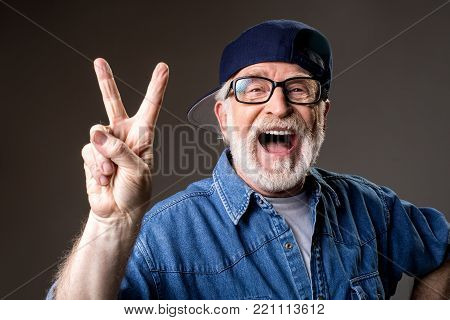 Portrait of cheery greybeard in cap showing peace sign and laughing. Isolated on grey background
