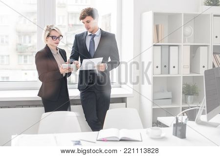 Portrait of two successful business people man and woman, discussing work standing at window in modern office behind glass wall, copy space
