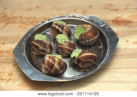 Escargots de Bourgogne on a metal plate ready to put in the oven