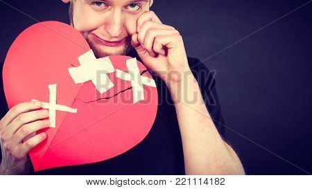 Bad relationships, breaking up, sadness emotions concept. Very sad young man holding broken heart made of paper.