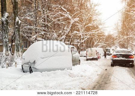 Car trapped on a street covered with big snow layer after heavy snowfall. Extreme blizzard aftermath