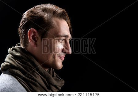 Side view profile of positive young trendy man is standing and looking forward with slight smile. Isolated background and copy space in right side