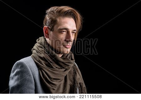 Young trendy wistful guy is standing and looking aside dreamily. Isolated background and copy space in right side