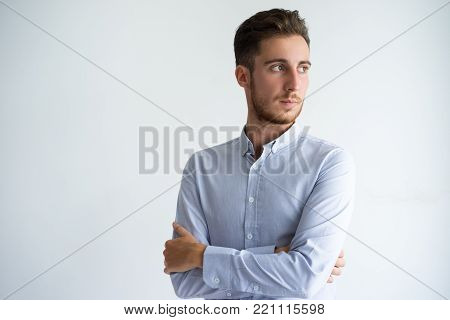 Portrait of serious young Caucasian businessman wearing shirt standing with folded arms and looking away. Confidence and career concept