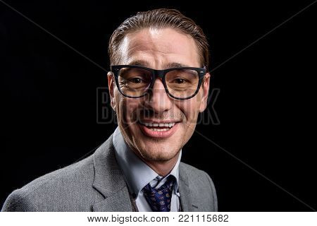 Full of joy. Portrait of easygoing optimistic young male entrepreneur in glasses is standing and looking at camera with smile. Isolated background