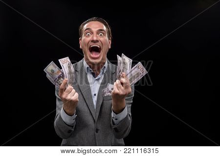 I am crazy about money. Portrait of young insane businessman is holding cash and looking at camera with wide-eyed. He is standing against dark background and screaming. Isolated