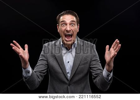 It is impossible. Portrait of overwhelmed businessman is standing and screaming with horror. He is looking at camera with panic while raising arms up. Isolated on background