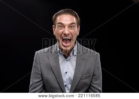Feeling anger. Portrait of irritated young businessman is standing and looking at camera while shouting with aggression. Isolated background