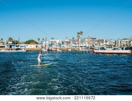 NEWPORT BEACH, CALIFORNIA - 4 NOVEMBER 2017: Man on paddle board by car ferry on Balboa Island, Newport Beach in California