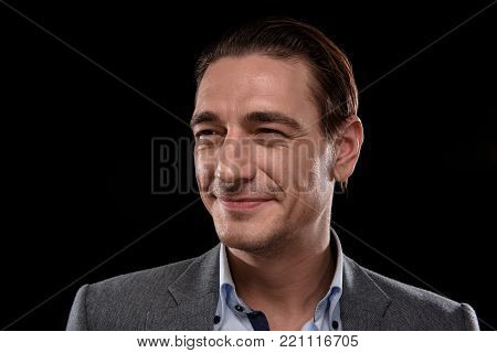 I know my goal. Portrait of optimistic successful young businessman. He is standing and looking aside with smile. Isolated background