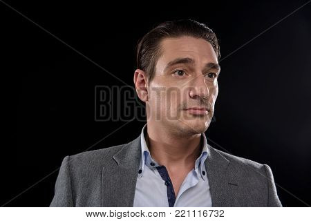 Portrait of wistful elegant young male entrepreneur is standing and looking aside pensively. Isolated on black background