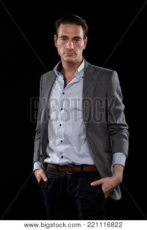Smart and confident. Portrait of elegant young businessman wearing formal clothes is standing with hands in pockets of his pants. He is looking at camera decisively. Isolated background