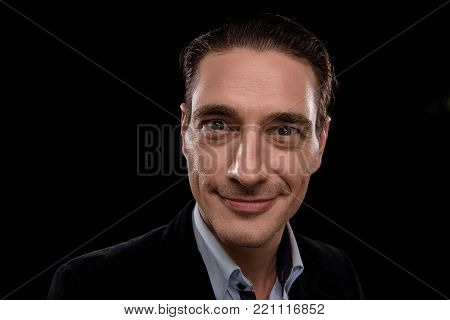 Great wonder. Portrait of optimistic qualified young businessman. He is standing and looking at camera with smile while feeling success. Isolated background