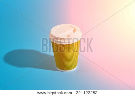 Hot coffee in green paper cup with white lid on blue background with shadow, blurred and soft focus image. Still life. Copy space. Sun flare