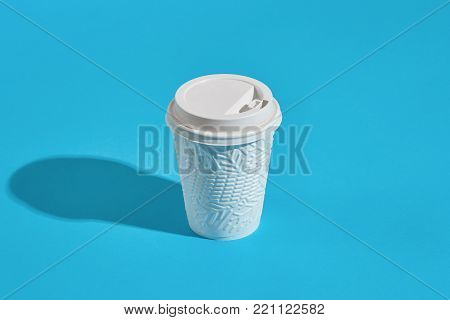 Hot coffee in white winter paper cup with lid on blue background with shadow, blurred and soft focus image. Still life. Copy space