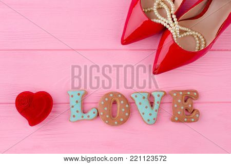 Word love from baked cookies. Red heart shaped velvet gift box and female leather shoes. Beautiful Saint Valentines Day composition on pink wooden background. Love and marriage concept.