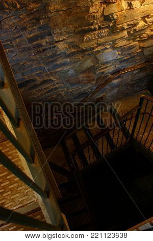 Dimly lit stairwell curls into the darkness