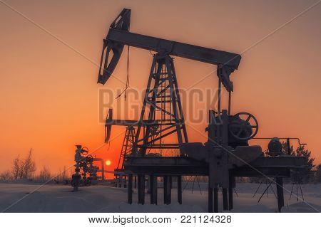 Inoperative Oil pump. Industrial landscape. Oil pump at sunset.