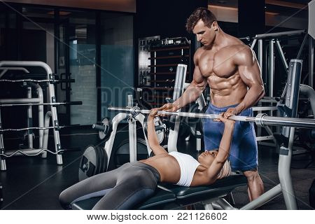 Personal trainer helping a young woman lift a barbell while working out in a gym. Personal trainer with a gorgeous body without a T-shirt in the gym