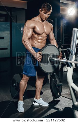 Handsome power athletic man on diet training pumping up muscles with dumbbell and barbell. Strong bodybuilder, perfect abs, shoulders, biceps, triceps and chest at the gym