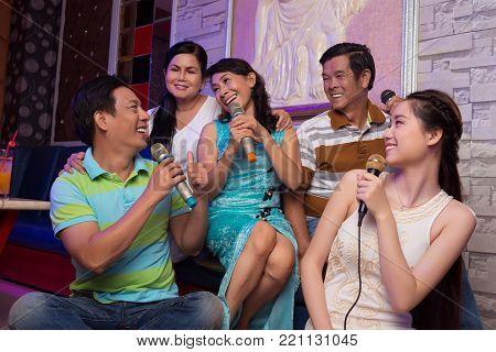 Big Vietnamese family singing together in karaoke