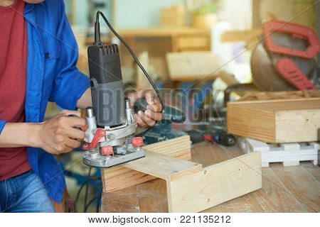 Carpenter using palm sander to finish work