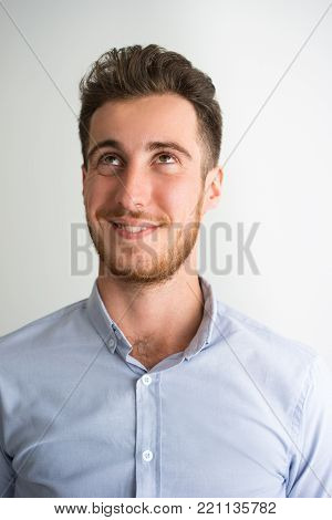 Portrait of young Caucasian businessman wearing shirt sneering and looking away. Dreaming and aspiration concept