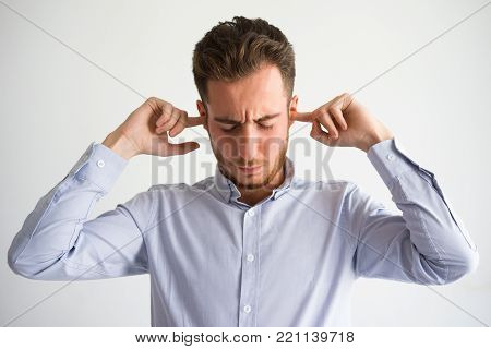 Portrait of irritated young Caucasian businessman wearing shirt plugging ears with fingers. Do not want to hear concept