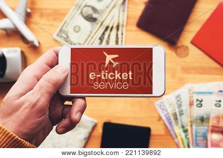 Man buying electronic ticket for airplane with mobile phone app and checking in for the flight. Overhead view of male hand with smartphone.